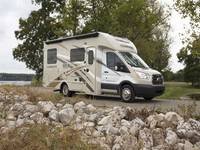 All white Thor Motor Coach Compass Motorhome parked in rocky field next to tree, mid day