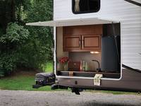 Forest River Wildwood Travel Trailer Exterior Kitchen on day lit campground.