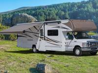 Winnebago Minnie Winnie Motorhome with Awning parked in sunny field in mountains